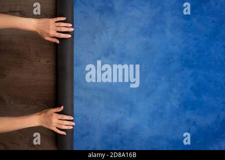 Primo piano delle mani della donna pieghevole yoga blu o tappetino fitness dopo l'allenamento a casa. Stile di vita sano, mantenere i concetti in forma. Vista dall'alto.