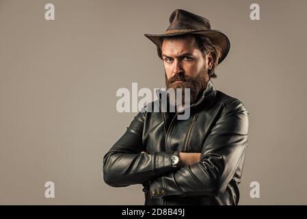 Couture dei cowboy. Stile di vita moderno occidentale. Uomo brutale e serio. Uomo bello e riuscito nel cappello dei cowboy. È in pelle giacca. Uomo di successo di stile biker. uomo occidentale indossare pelle. Foto Stock