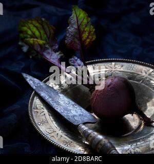 Barbabietola fresca intera con fogliame posto su piatto d'annata con coltello da cucina su sfondo nero