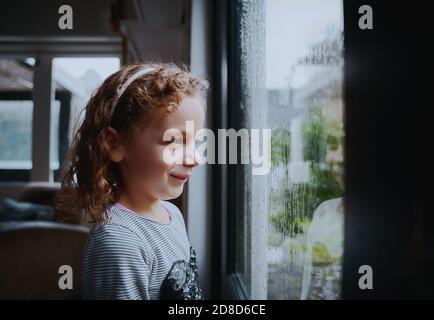 Ragazza felice con sorriso carino godendo guardando la pioggia da finestra a casa Foto Stock