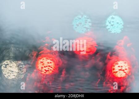 Vista astratta dei colorati cerchi di bokeh in verde e rosso colori oscuri del traffico sera su fondo di luci di strada con bagnato gocce di pioggia sul parabrezza di Foto Stock
