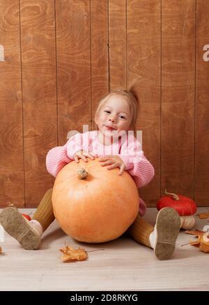 una ragazza carina piccola in un maglione rosa abbraccia un grande zucca seduta sul pavimento su uno sfondo di legno Foto Stock