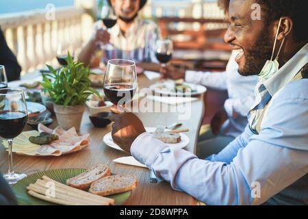 Allegri amici multirazziali che mangiano e bevono vino mentre indossano protettivo Maschere - Focus su uomo nero
