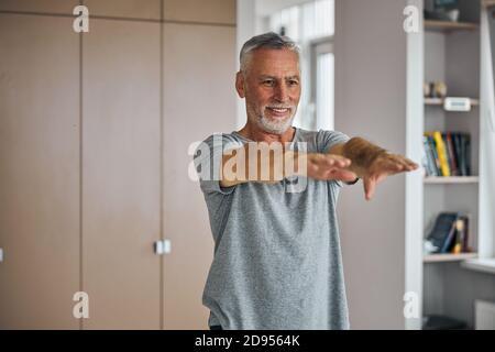 Gladsome uomo anziano che si esercita a casa e si allunga