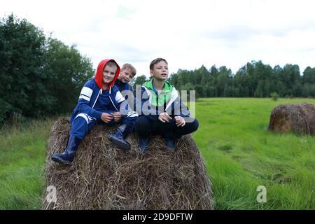 Tre bambini seduti su uno stack di paglia in estate