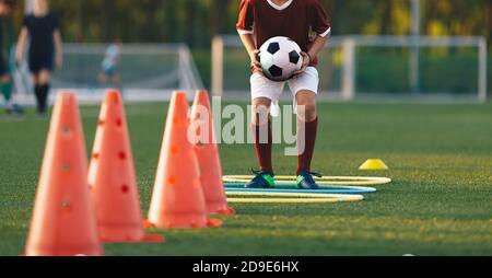 Primo piano ragazzo che corre sul campo di allenamento del calcio con la palla in mano. Giocatore che salta sopra gli ostacoli. Corso di allenamento di calcio ostacoli. Bambini leven