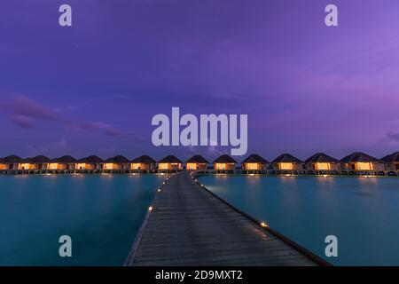 Bungalow sull'acqua nelle isole Maldive. Paradiso tropicale isola destinazione, luci LED con lungo molo sotto il cielo notturno crepuscolo. Paesaggio esotico