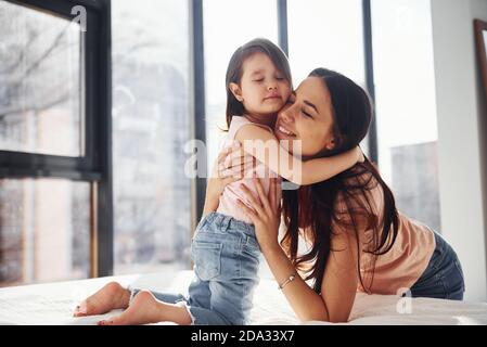 Giovane madre con la figlia che si abbracciano a letto
