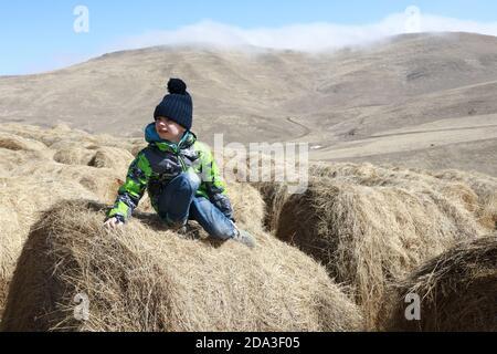 Bambino seduto sulla balla di fieno in fattoria, Kabardino-Balkaria, Russia