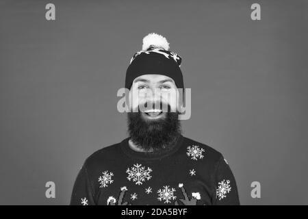 Giornate fredde. Vacanze invernali. Uomo Barbuto hipster usura inverno berretto lavorato a maglia. Barbiere e dei peli del viso. In inverno la cura della pelle. Ragazzo indossa abbigliamento invernale e accessori. Faccia barbuta chiudere su sfondo rosso. Foto Stock