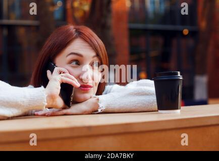 Donna appesa su un telefono con espressione di sopracciglia sollevata sul suo viso. Concetto di chat con gli amici.