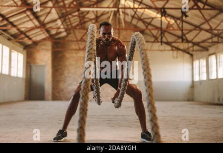 Fitness man allenarsi con la corda di battaglia in palestra cross training all'interno del vecchio magazzino. Uomo muscolare che lavora fuori a magazzino vuoto.