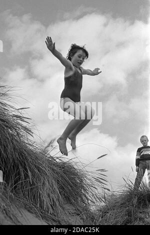 Giovane ragazza che salta da una duna, ragazzo giovane che la guarda, 1986 settembre, Irlanda
