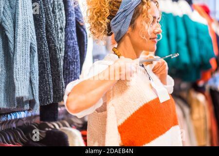 Felice donna che prova e indossa un nuovo maglione per la stagione invernale in un negozio - concetto di shopping e vendite - la gente acquista giacche colorate Foto Stock