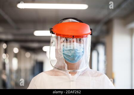 Coronavirus COVID-19 malattia del virus epidemia globale epidemia, UK NHS Frontline medico chiave lavoratore, EMS Personal Protective Equipment, parcheggio corridoio,