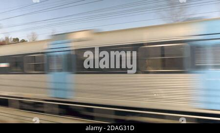 Sentiero in movimento Tram sulla ferrovia, treno ad alta velocità in movimento sulla ferrovia, con effetto di sfocatura del movimento. Sfondo a lunga esposizione Foto Stock