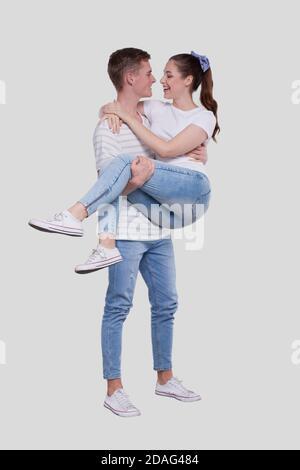 Uomo che tiene la ragazza nelle sue braccia. Coppia in piedi isolata. Bella coppia che si guarda l'un l'altro. Foto Stock