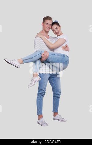 Uomo che tiene la ragazza nelle sue braccia. Coppia in piedi isolata. Bella coppia che guarda alla fotocamera. Foto Stock