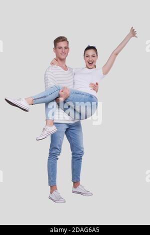 Uomo che tiene la ragazza nelle sue braccia. Coppia in piedi isolata. Bella coppia che guarda alla ragazza della macchina fotografica è felice che tiene la mano in su. Carino coppia, Famiglia Foto Stock