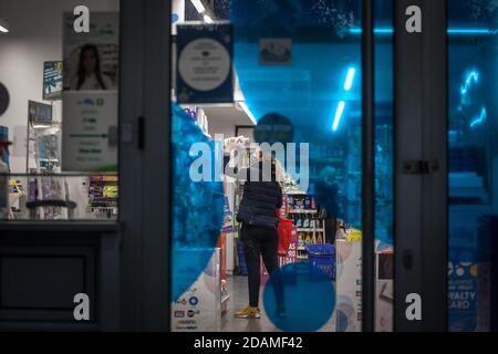 BELGRADO, SERBIA - 10 OTTOBRE 2020: Donna, collaboratore di una farmacia farmacia farmacia, che tiene prodotti indossando maschera di protezione su Coronavir Foto Stock
