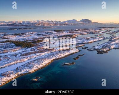Catena montuosa innevata sette Sorelle, De syv sostre, Sju sostre, di fronte all'arcipelago invernale in mare, Donna, Nordland, Norvegia