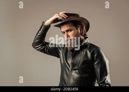Stile Cowboy. Uomo alla moda vestito con giacca in pelle. Modello di moda occidentale. Uomo bello con cappello da cowboy. Motociclista serio con cuscinetti. Uomo maturo elegante e moderno. guardaroba occidentale uomo da uomo. Foto Stock