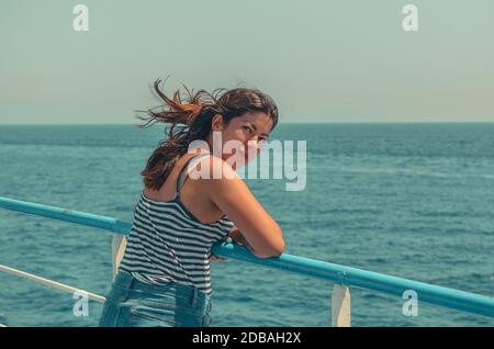 giovane ragazza allegra con capelli neri in una t-shirt a righe e jeans blu si erge sul ponte di una nave in mare
