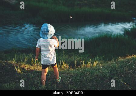 Indietro immagine di un ragazzo caucasico con cappello blu gettare le pietre nel lago durante una passeggiata estiva