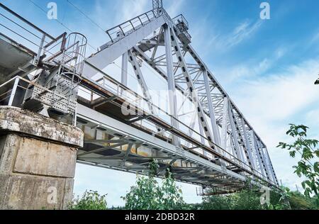 Ponte del treno di ferro sul fiume contro un cielo nuvoloso. Ponte nel verde Foto Stock