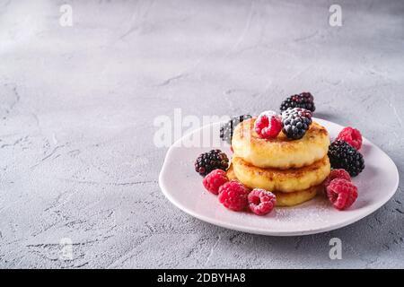 Frittelle al formaggio di cottage e zucchero in polvere, frittelle di cagliata dessert con lampone e bacche di mora in piastra su fondo di cemento di pietra