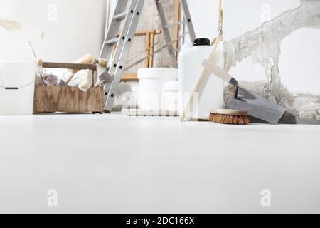 Basso angolo di ripresa interna di cantiere o cantiere di rinnovamento domestico con gli attrezzi sul pavimento bianco con copia spazio