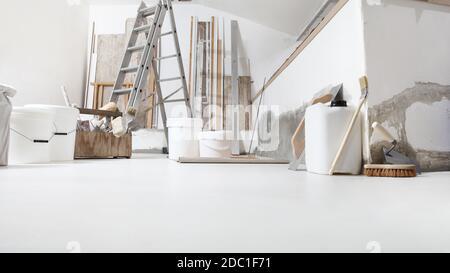 Basso angolo di ripresa interna di cantiere o cantiere di rinnovamento domestico con gli attrezzi sul pavimento bianco con vernice secchi e primer lattino jerry