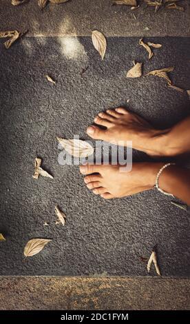 Benvenuto autunno sfondo. Closeup Concept Foto di una donna a piedi nudi piedi e foglie secche. Tema della stagione autunnale. L'estate è finita. Foto Stock