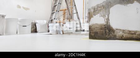 Basso angolo di ripresa interna di cantiere o cantiere di rinnovamento domestico con gli attrezzi con i secchi di vernice su bianco pavimento con spazio per la copia