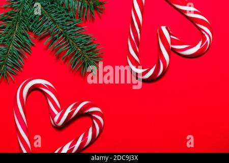 Cuori di Lollipop su superficie rossa con rami di albero di Natale. Biglietto d'auguri per Natale e Capodanno Foto Stock