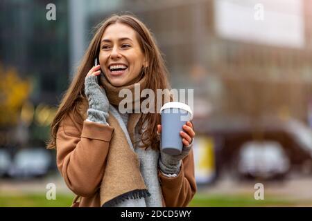 Giovane donna sorridente con smartphone e tazza da caffè all'aperto in ambiente urbano
