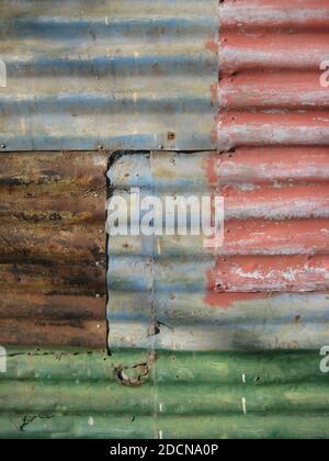 parete realizzata in lamiera grecata con diversi colori sbiaditi e ruggine, fondo testurizzato Foto Stock