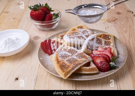 Un primo piano di deliziosi waffle belgi con fragole coperte zucchero in polvere sulla tavola Foto Stock