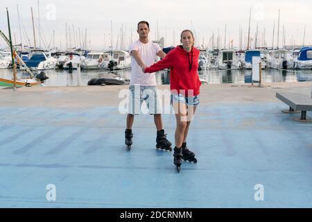 Giovane coppia felice pattinaggio a rotelle in skate Park vicino al bellissimo porto in estate.Friendship sport e fitness stile di vita concetto.