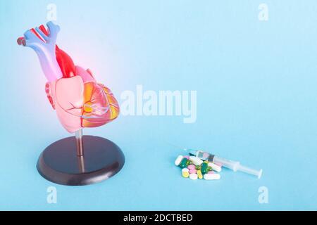 Simulate il cuore umano, le pillole e la siringa su uno sfondo blu. Concetto di trattamento delle malattie cardiache con farmaci, farmacoterapia, spazio di copia per il testo,
