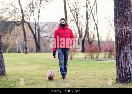 L'uomo con maschera facciale prende il suo cane per una passeggiata vicino a casa durante il coronavirus. Si prende cura del suo animale domestico. Brevi passeggiate durante il coronavirus. Quarantena con un