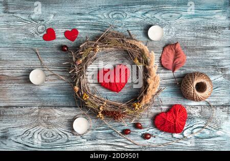Composizione romantica con cuori rossi, corona e candele su sfondo naturale di legno. Foto Stock
