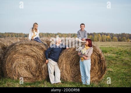 Coppia senior con nipoti seduti su balle di fieno sul campo durante il fine settimana