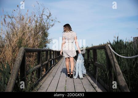 Vista completa sul retro del corpo di una giovane donna in un abito casual con giacca a mano che passeggiano sul ponte pedonale in legno tra l'alto erba secca in giornata di sole Foto Stock
