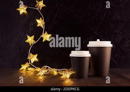 Due tazze da caffè in carta nera vuota da togliere con luci dorate di natale illuminanti con stelle in interni scuri, mock up per la pubblicità, caffè, bar,