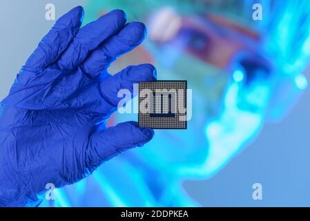 Un ingegnere che lavora in un laboratorio indossando una speciale uniforme e guanti protettivi detiene il nuovo processore in mani e lo esamina