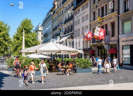 Le persone passeggiano o bevono un drink sulla terrazza di un caffè Starbucks in Place de Longemalle a Ginevra, di fronte all'hotel de la Cigogne. Foto Stock