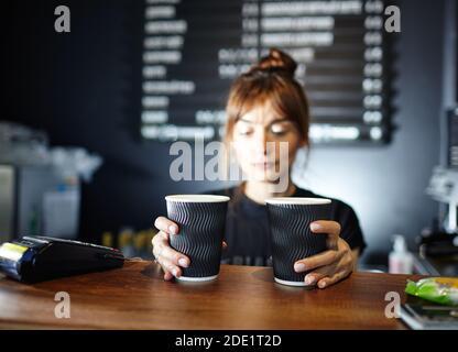 Il barista può contenere due tazze di carta monouso di caffè nella caffetteria. Immagine sfocata, messa a fuoco selettiva