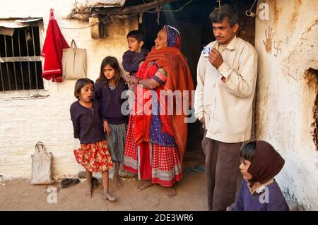 Family in their home entrance - Village in Rajasthan, India
