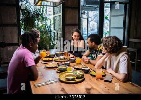 Un gruppo multiculturale di giovani in un caffè, mangiare cibo asiatico, bere cocktail, chiacchierare.